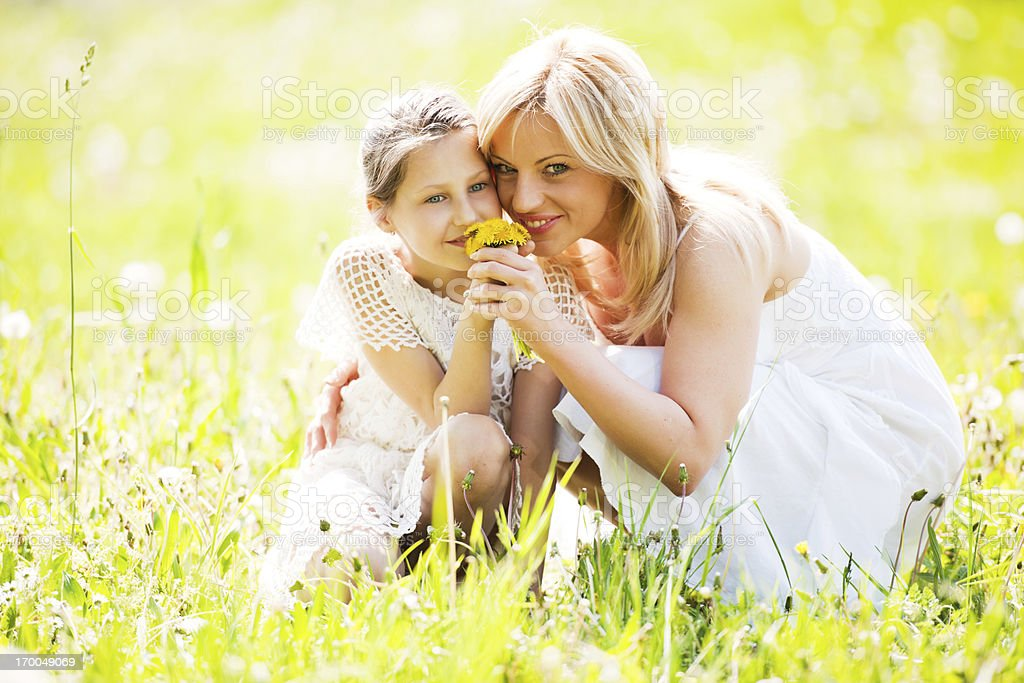Mother and daughter smelling the flowers in nature. stock photo