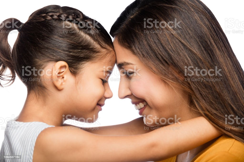 Mother and daughter smiling face to face stock photo