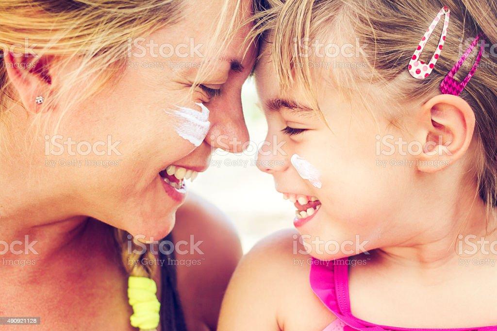 Madre e hija sonriendo juntos con protector solar en su orejetas - foto de stock