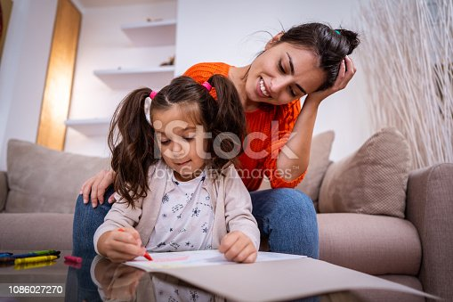 Cute girl is drawing with wax crayons while mother is watching her.