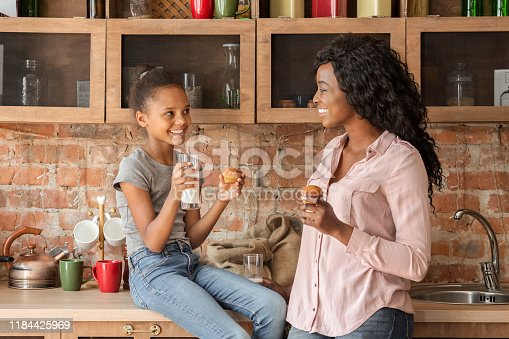 Cheerful african mother and daughter spending time together, drinking milk and eating cupcakes in kitchen