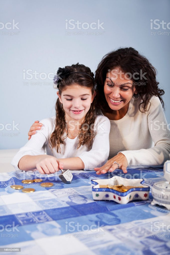 Mother and daughter spinning dreidl stock photo