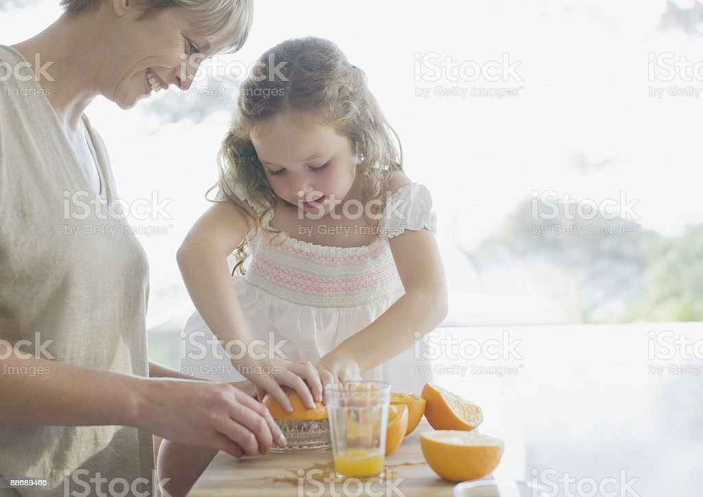 Mother and daughter squeezing oranges royalty-free stock photo