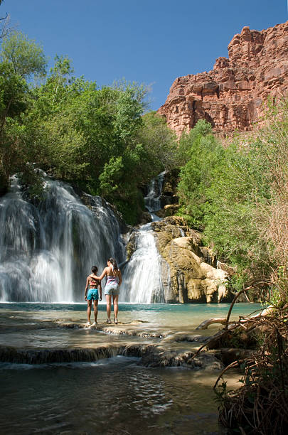Mother and Daughter Standing in Front of Navajo Falls stock photo