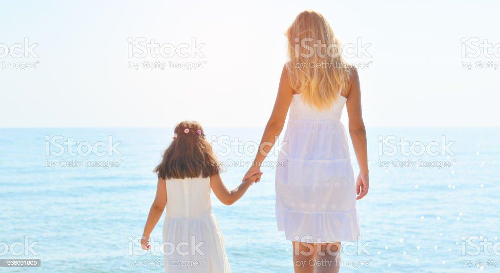 Mutter und Tochter stehen am Strand und Sonnenuntergang – Foto