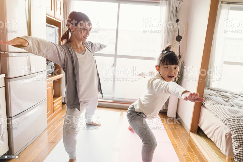 Mother and daughter stretching at home stock photo