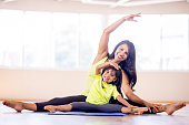 A mother and daughter are doing yoga together at the gym. They are stretching on a yoga mat and are smiling while looking at the camera.