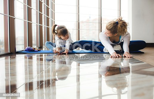 istock Mother and daughter stretching on a yoga mat at the gym 466808392