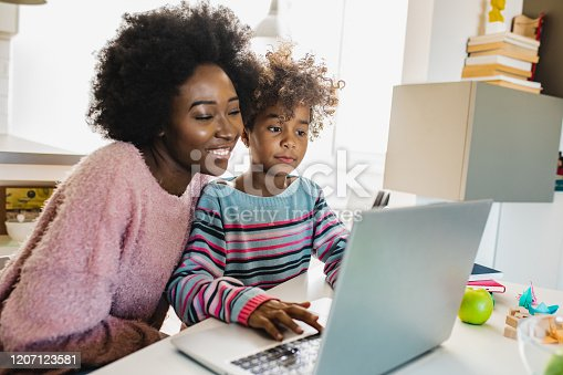 African American mother is teaching her daughter are using laptop at home together