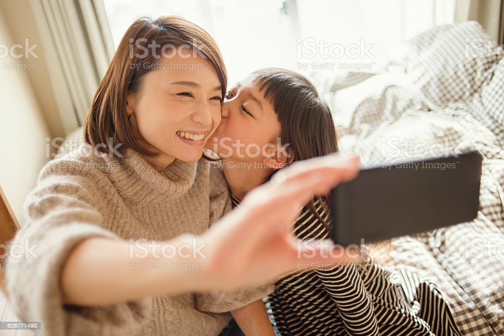 Mother and daughter taking a selfie in bed room stock photo