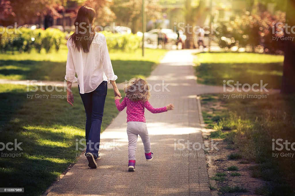 Mother And Daughter Taking A Walk In The Park stock photo