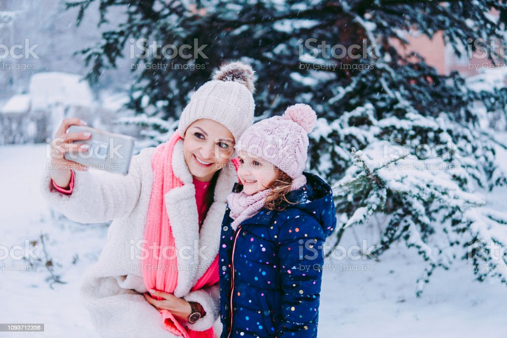 Mother and daughter taking selfie in winter park stock photo