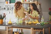 Mother and daughter enjoying making lemonade together at home.