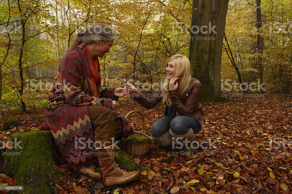 Mother and daughter talking in forest stock photo
