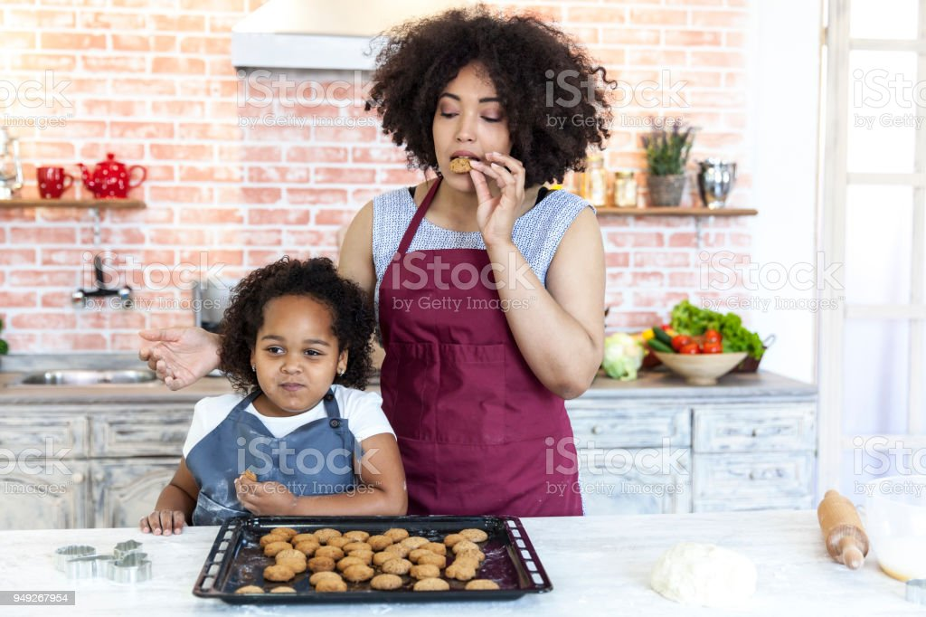 Mother and daughter tasting cookies stock photo