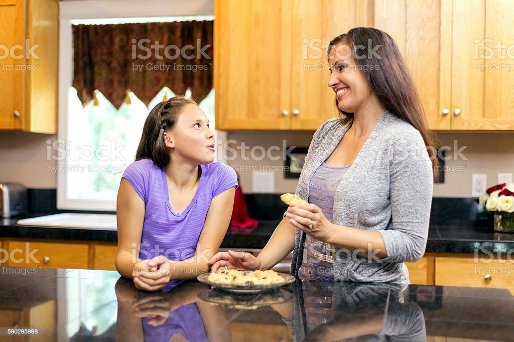 Mother and daughter tasting homemade cookies royaltyfri bildbanksbilder