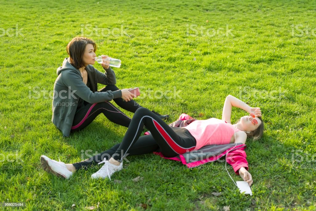 Mother and daughter teenager resting after workout stock photo