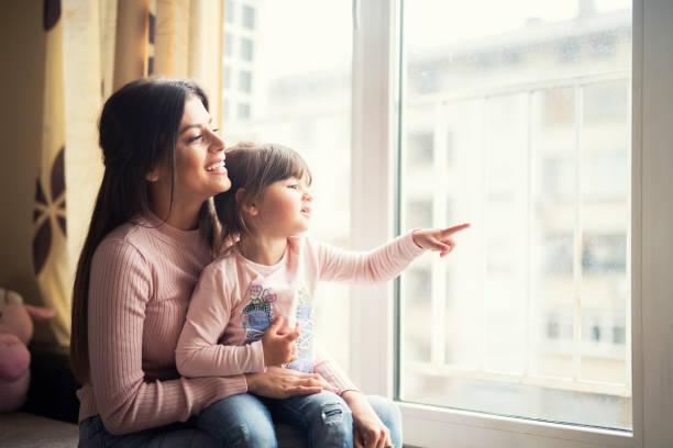 어머니와 딸은 함께 집에서 창문을 보고 행복 하 게 웃 고 있습니다. - 창문 너머로 봄 뉴스 사진 이미지