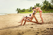 A DSLR Canon photo of  a cute 8 year old daughter tenderly playing with her beautiful mother at idyllic deserted Toque Beach in São Miguel dos Milagres, Alagoas, Northeastern Brazil. The mother is sitting on a beach chair looking up while her daughter is coming from behind lowering her face until their noses are touching.