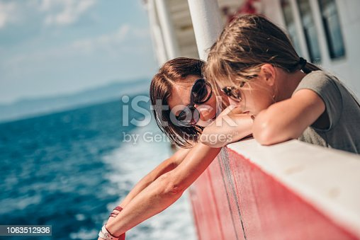 Mother and daughter traveling on a ferry boat and standing on a ship deck on a sunny day