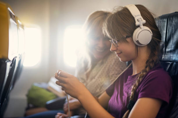 Mother and daughter travelling by plane stock photo