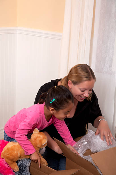 mother and daughter unpacking in a new home - happy mom packing some toys stock photos and pictures