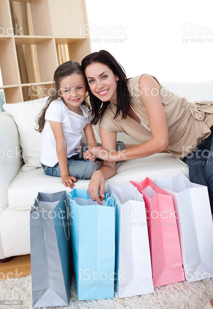 Mother and daughter unpacking shopping bags in the living-room royalty-free stock photo