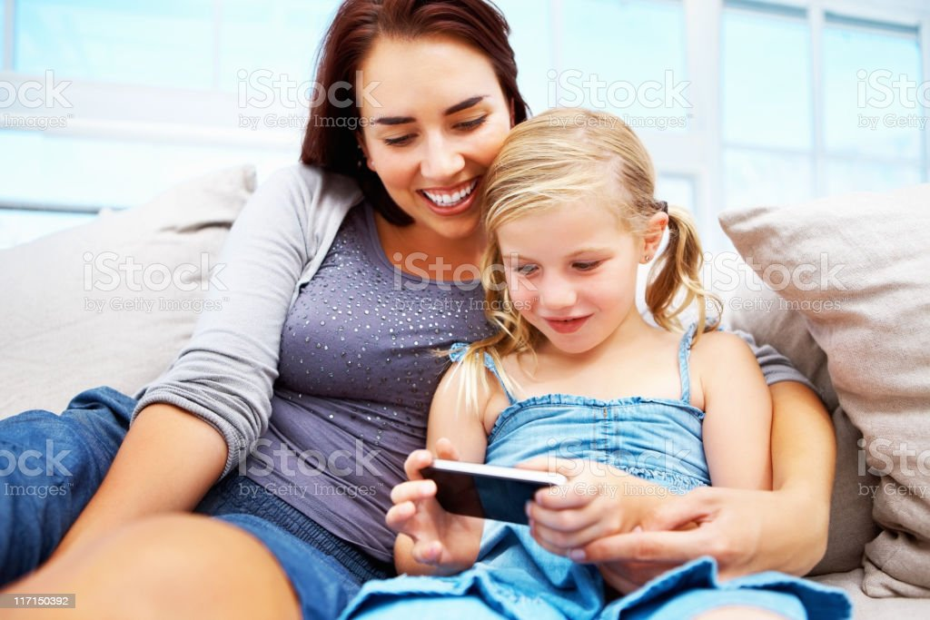 Mother and daughter using a cell phone on couch royalty-free stock photo