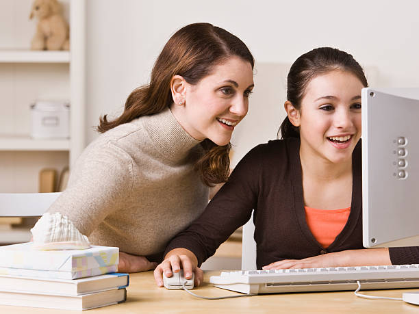A mother and daughter using a computer together stock photo