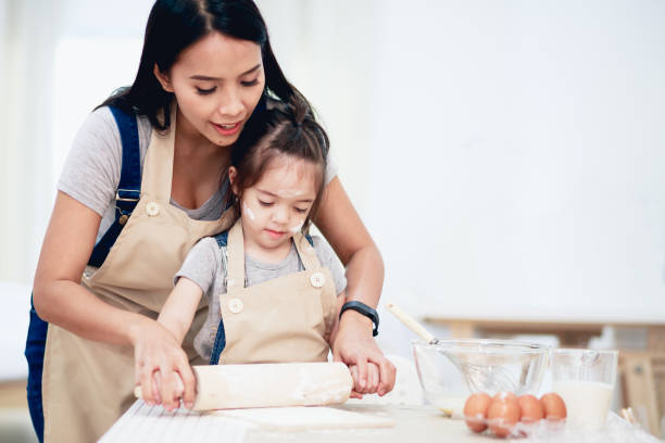 Mother and daughter using a rolling pin together stock photo