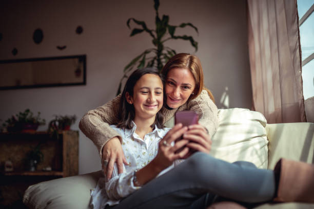 Mother and daughter using a smartphone Mother and daughter sitting on a couch at home using a smartphone parent stock pictures, royalty-free photos & images