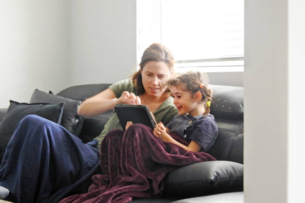 Mother and daughter using a tablet in living room while forced to stay at home because government policies efforts to prevent pandemic coronavirus (COVID-19) spreading stock photo