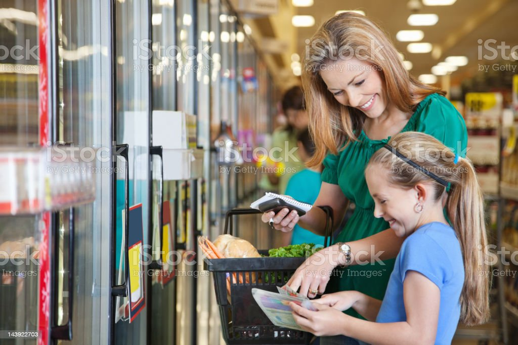 Mother and daughter using coupons at the grocery store stock photo