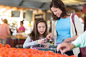 Mid adult Caucasian brunette woman is teaching her elementary age daughter how to shop with coupons. Mother and daughter are saving money while shopping for local produce in small market. Customers are pushing shopping cart near bin of tomatoes in produce section.
