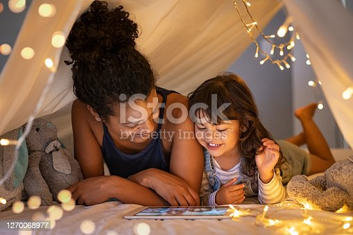 istock Mother and daughter using digital tablet inside illuminated cozy hut 1270068977