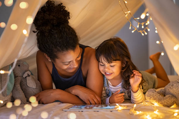 Mother and daughter using digital tablet inside illuminated cozy hut stock photo