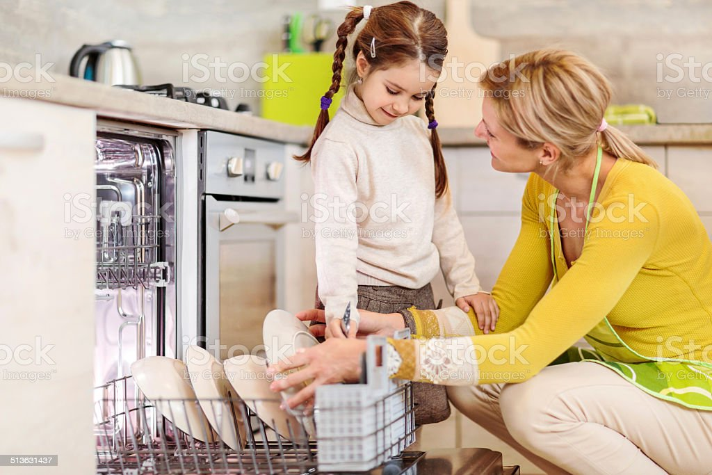 Mother and daughter using dishwasher. stock photo