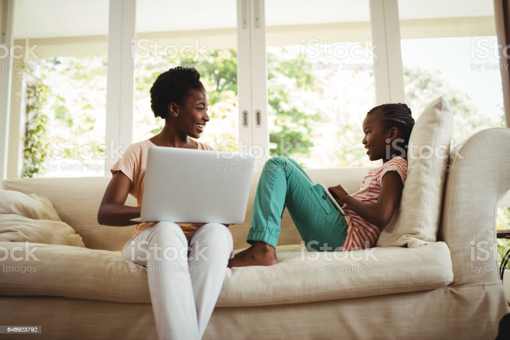 Mother and daughter using laptop and digital tablet stock photo