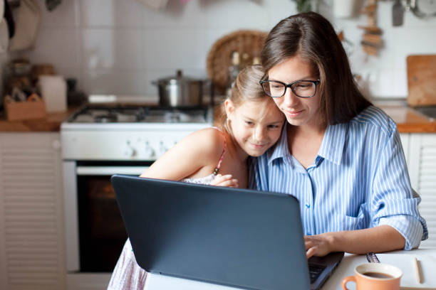 Mother and daughter using laptop and Internet. Freelancer workplace in cozy kitchen. Woman and child stock photo