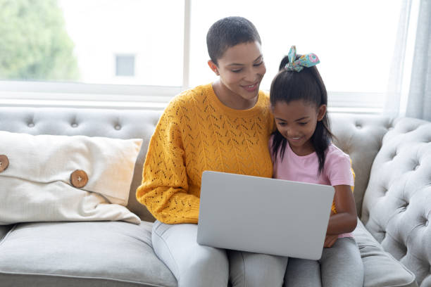 Mother and daughter using laptop on a sofa in living room stock photo