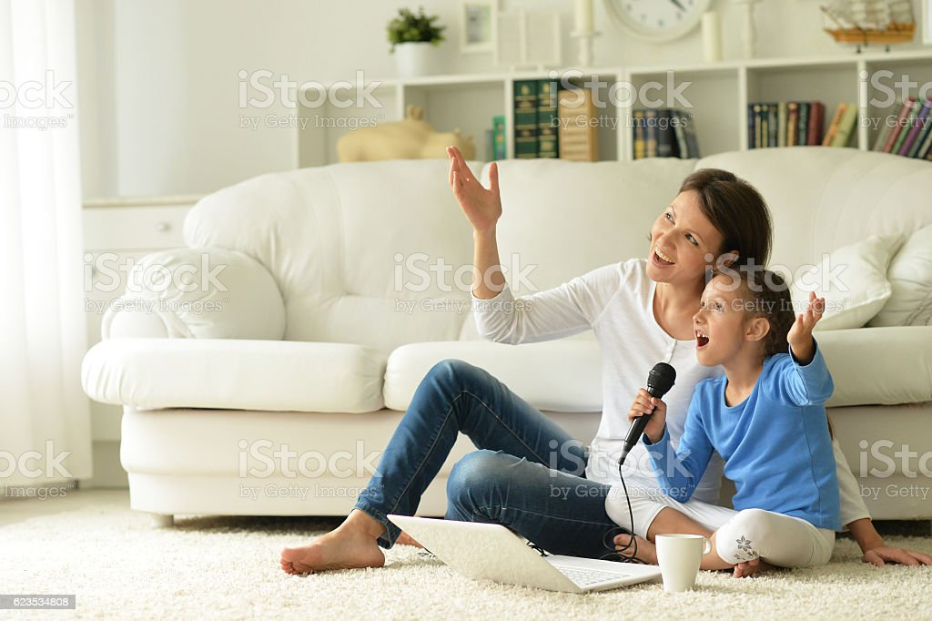 mother and daughter using laptop stock photo