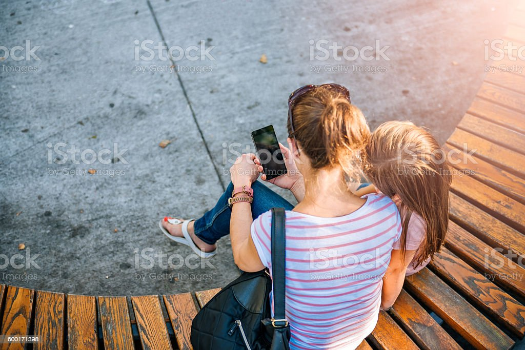 Mother and daughter using phone in the park stock photo