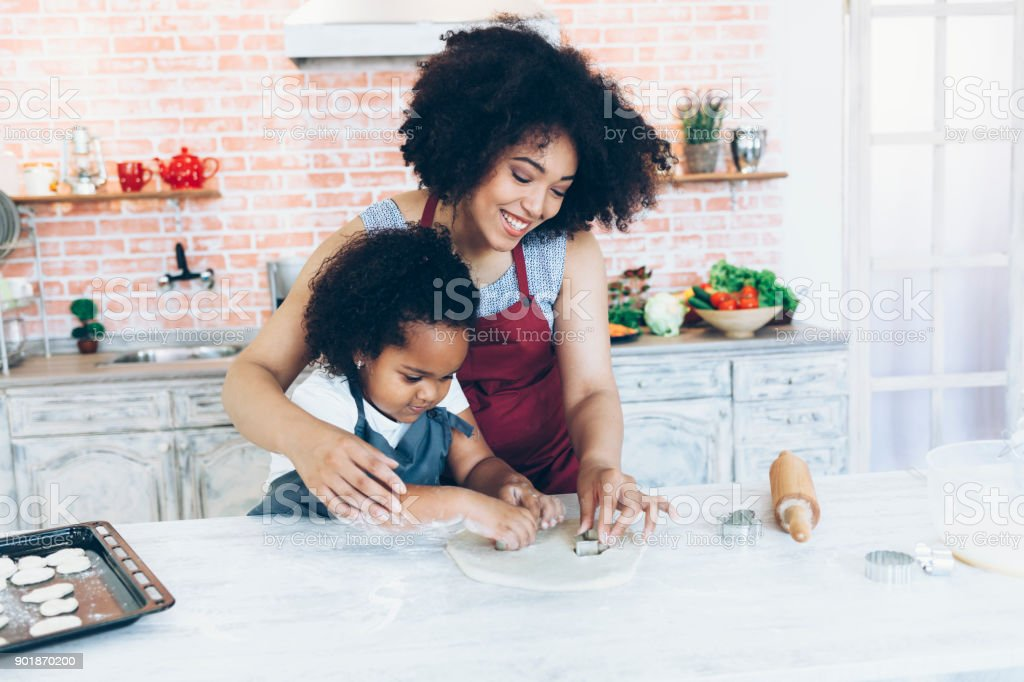 Mother and daughter using rolling pin and making biscuits stock photo