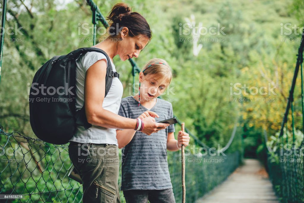 Mother and daughter using smart phone on the wooden bridge stock photo