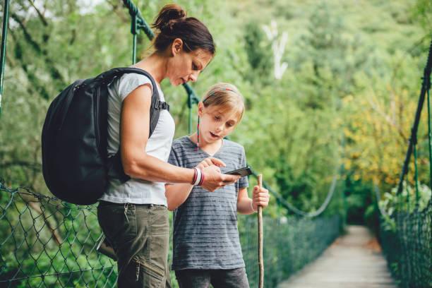 母と娘の木製の橋でスマート フォンを使用して - 自然旅行 ストックフォトと画像