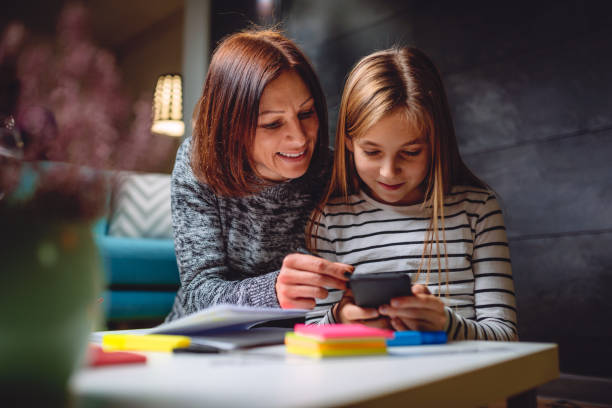 mother and daughter using smart phone - kids phones stock photos and pictures