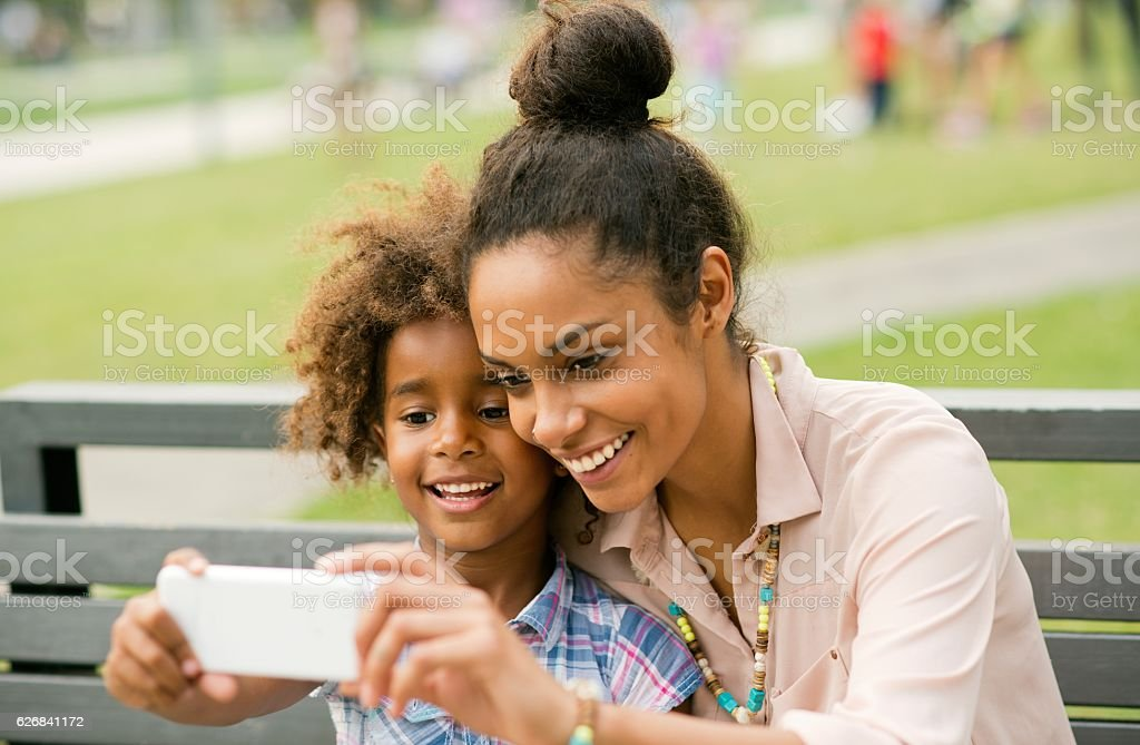 Mother and daughter using smartphone. stock photo