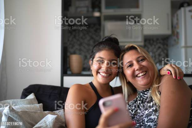 Mother and daughter using smartphone while they are sitting on the picture id1132119076?b=1&k=6&m=1132119076&s=612x612&h=skshwwv67 sfmtuvixxjj9go6thy vli hagl30qp4i=