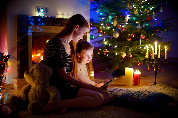 mother and daughter using tablet by fireplace on christmas - weihnachten videos stock-fotos und bilder