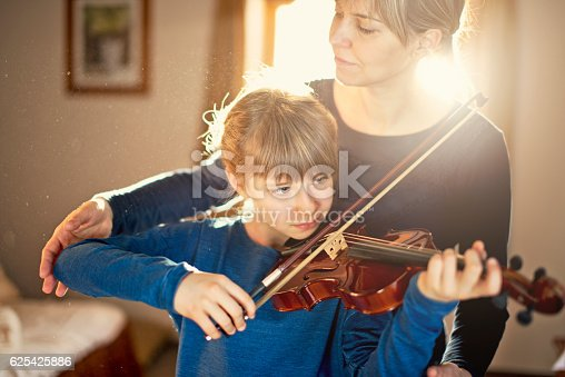 Little girl aged 9 is practicing violin in the morning. Mother is helping her by correcting her posture. The morning sun is backlighting them through the window.